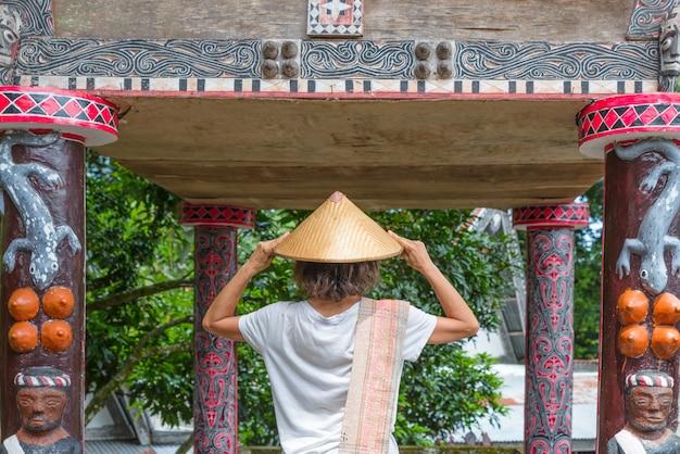 Tourist mit dem traditionellen asiatischen hut, der traditionelles dorf batak und altes grab von könig sidabutar im tomok see toba, berühmtes reiseziel in sumatra, indonesien besucht.