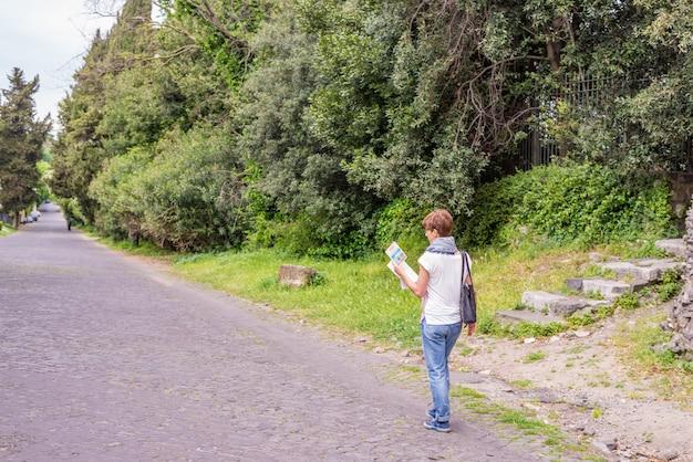 Tourist mit der karte, die um alte ruinen in alter stadt roms erhält