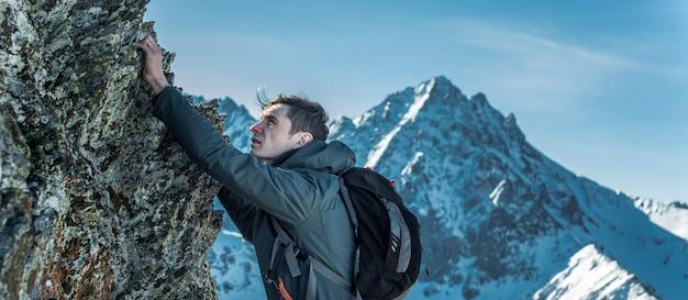 Tourist mit einem rucksack, der auf felsen zur spitze von bergen kriecht. motivation und zielerreichung