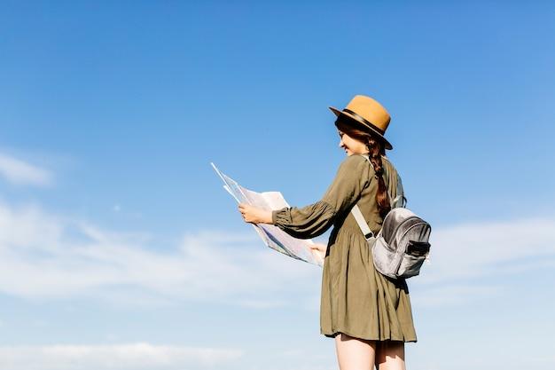 Tourist mit karte am sonnigen himmel hintergrund
