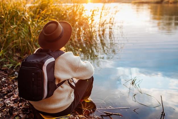 Tourist mit rucksack, der bei sonnenuntergang am ufer des flusses sitzt. ältere einsame frau, die sich entspannt und die natürliche frühlingslandschaft bewundert. reisekonzept