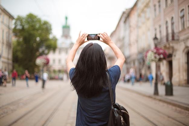 Tourist mit rucksack, der durch die innenstadt spaziert und auf dem smartphone fotografiert