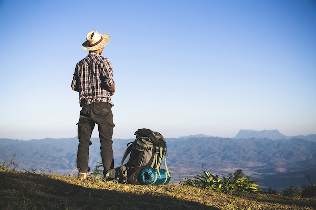 Tourist vom berggipfel. sonnenstrahlen. mann tragen großen rucksack gegen sonnenlicht