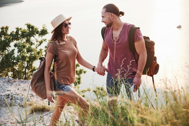 Tourist zwei mit rucksäcken klettern zur spitze des berges und genießen sonnenaufgang