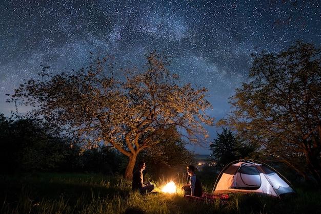 Touristen am lagerfeuer in der nähe von zelt in der nacht