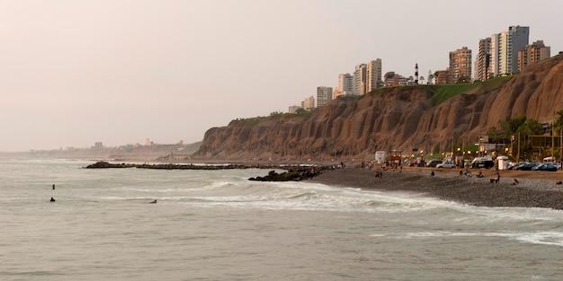 Touristen auf dem strand mit einer stadt im hintergrund, miraflores-bezirk, lima-provinz, peru