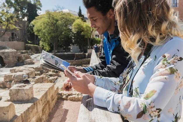 Touristen auf der karte vor römischen denkmal suchen