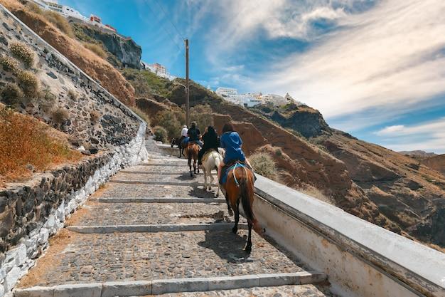 Touristen auf eseln steigen die treppe hinauf, fira, santorini