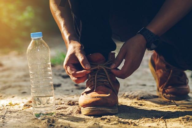 Touristen banden ihre schuhe auf einem waldweg mit einer wasserflasche an der seite fest