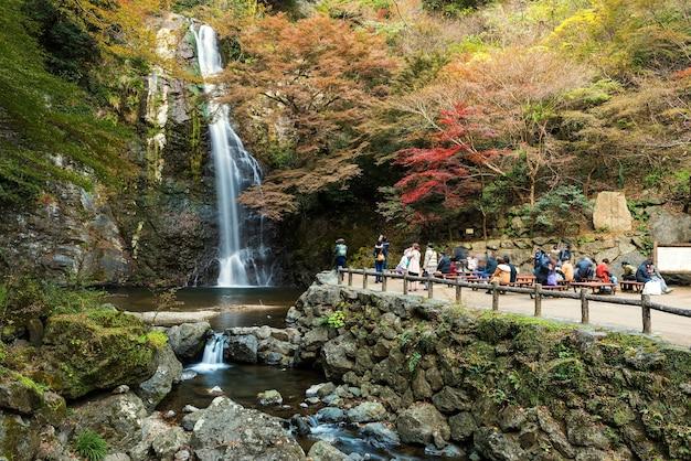 Touristen besuchen minoo wasserfall mit herbstlaubfarben