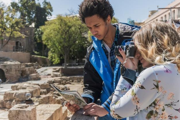 Touristen betrachten karte an einem sonnigen tag