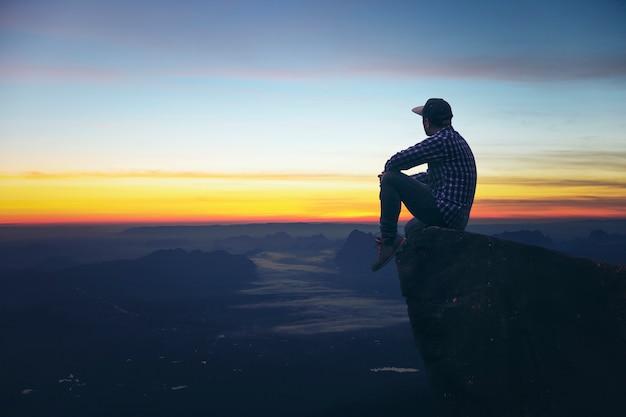 Touristen des jungen mannes sitzen an der oberseite des felsens schöner aussichtspunkt sonnenaufgang mit nebel.