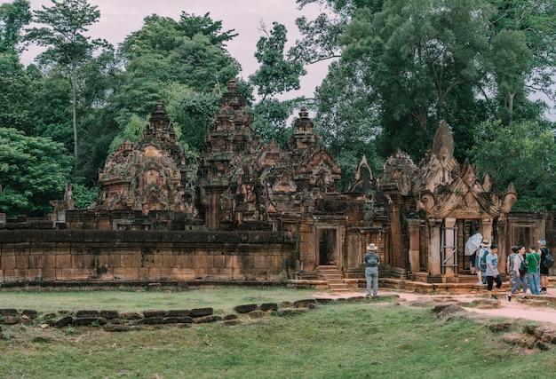 Touristen, die die ostgopura des zweiten geheges mit dem erstaunlichen geschnitzten giebel aus rotem sandstein im tempel banteay srei (zitadelle der frauen) in kambodscha bewundern.