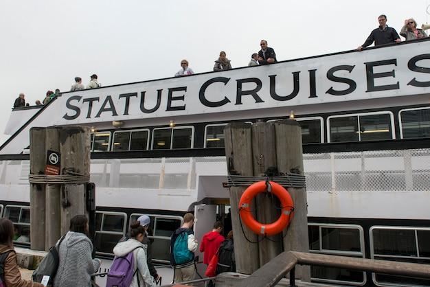 Touristen, die ein schiff zur freiheitsstatue, freiheits-insel, new- yorkhafen, manhattan, neues y einsteigen