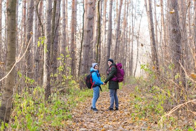 Touristen, die im park mit blau gekleidetem rucksack gehen