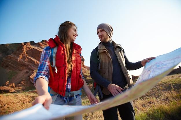 Touristen, die mit karte in berge reisen