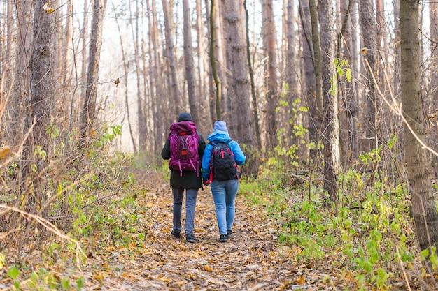 Touristen, die mit rucksack in blauen und schwarzen jacken im park spazieren gehen, rückansicht