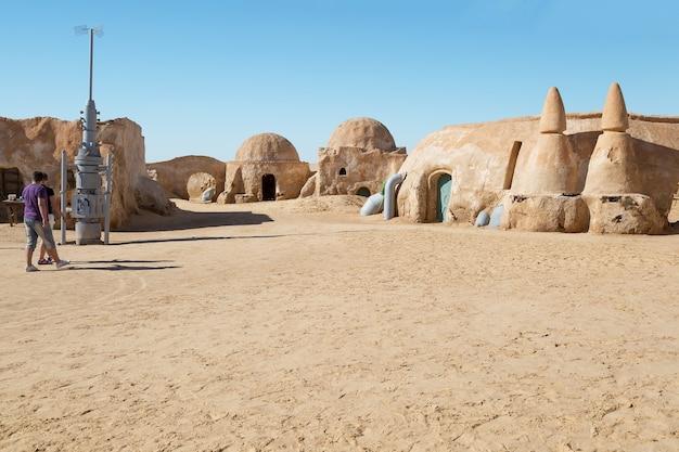 Touristen, die zwischen häusern vom planeten tatooine spazieren gehen, spielen für den star wars-film