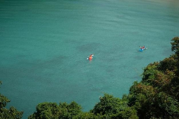 Touristen fahren kajak in der weiten see