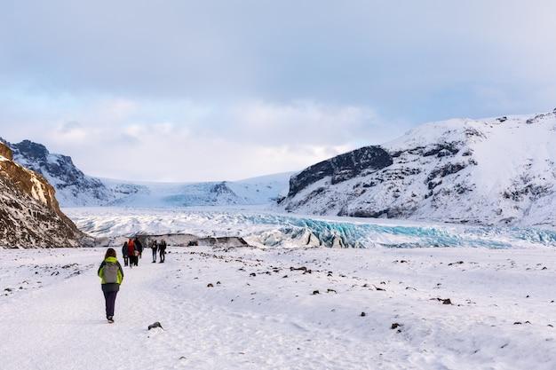 Touristen fahren zum gletscher auf dem panorama des isländischen gebirgsgletschers