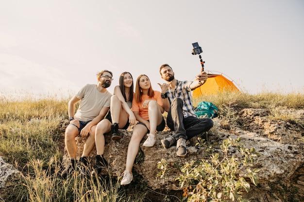 Touristen filmen vlog, der auf einer klippe in den bergen sitzt.
