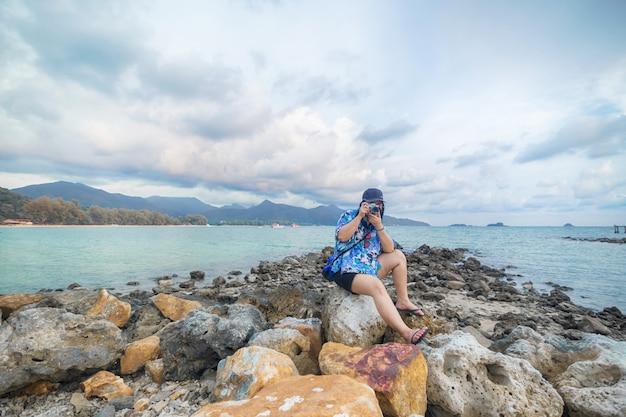 Touristen fotografieren auf den felsen am meer von koh chang.