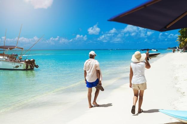 Touristen im sommeroutfit, die an der küste spazieren und die wundervolle zeit bewundern