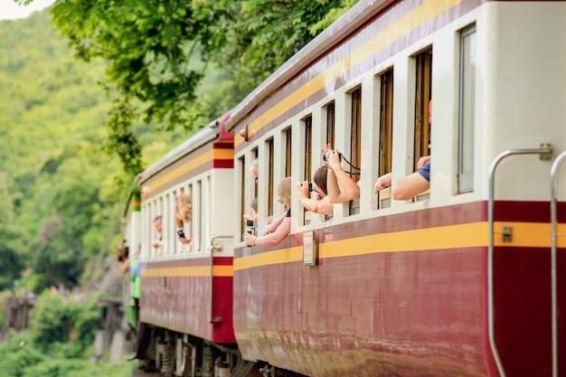 Touristen machen sie ein foto, wenn sie züge bereisen, die auf todeseisenbahnbrücke laufen, die kwai fluss in kanchanaburi kreuzt