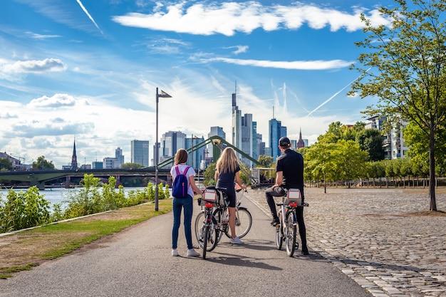 Touristen mit dem fahrrad erkunden die skyline von frankfurt am main.