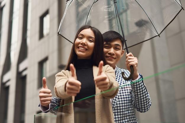 Touristen mit regenschirm jungen und mädchen zeigen daumen.
