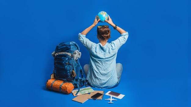 Touristen planen urlaub mit hilfe der weltkarte mit anderem reisezubehör.