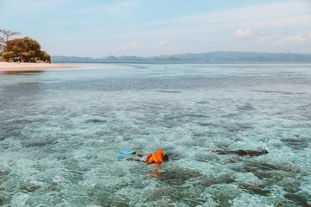 Touristen schnorcheln auf dem transparenten meerwasser mit schwimmweste