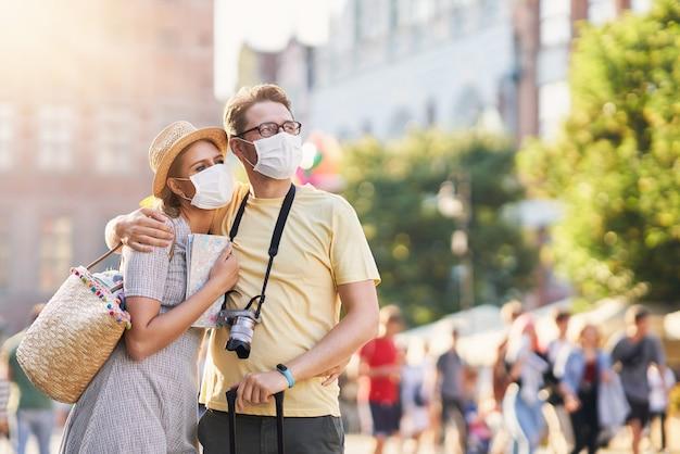 Touristen sightseeing in masken während der sommerferien mask