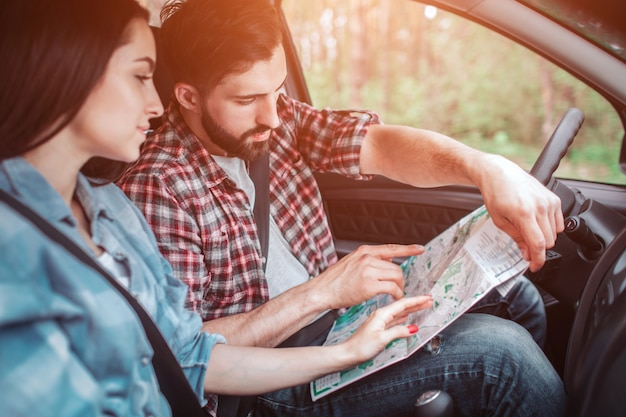 Touristen sitzen im auto und suchen nach karten. guy hält und zeigt darauf. mädchen zeigt auch.