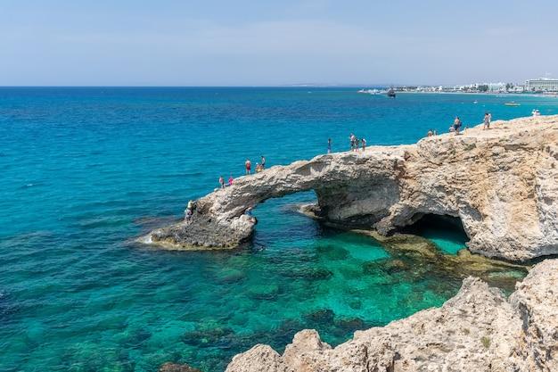 Touristen springen aus großer höhe in das azurblaue wasser des mittelmeers.