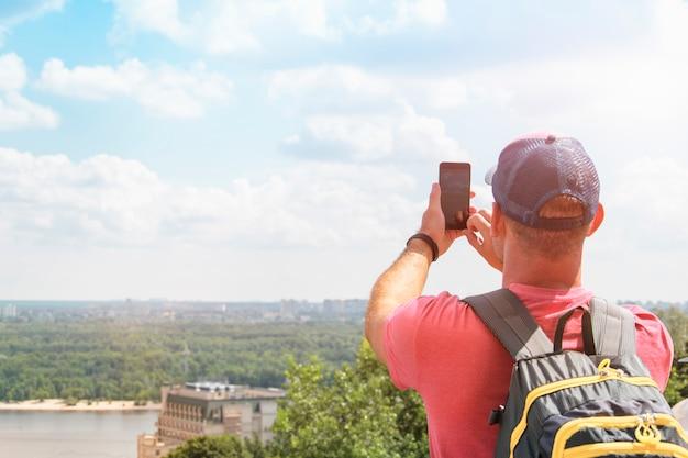Touristenfotos am telefon einen schönen blick auf die stadt. mann steht mit dem rücken