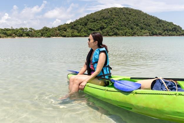 Touristenfrau, die auf kajak lookign am schönen tropischen strand im urlaub sitzt.