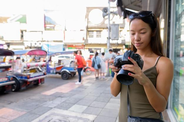 Touristenfrau, die die stadt bangkok an der khao san road erkundet
