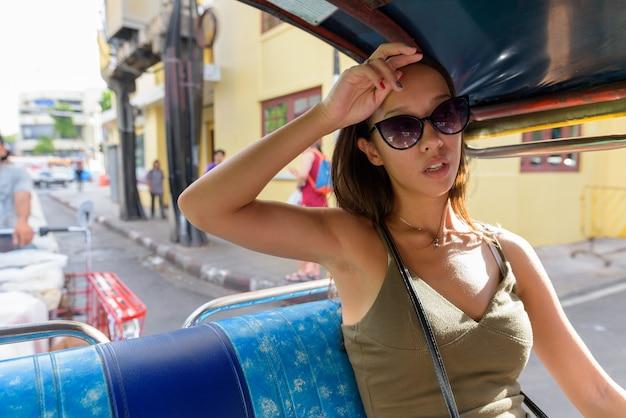 Touristenfrau, die die stadt von bangkok mit tuk-tuk-taxi erkundet