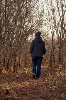 Touristenfrau, die entlang eines waldes geht