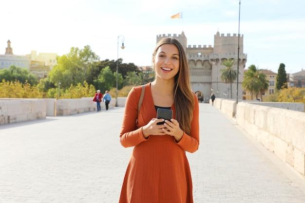 Touristenfrau, die in der stadt valencia geht, die smartphone betrachtet kamera betrachtet