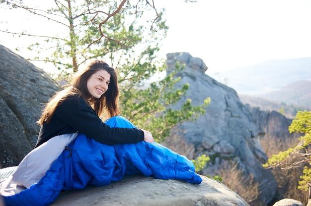 Touristenfrau in schlafsäcken auf großen felsen