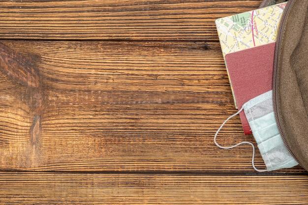 Touristenkarte, kreditkarte, reisepass, schutzmaske ragen aus dem reiserucksack auf dem hölzernen hintergrund mit kopienraum heraus