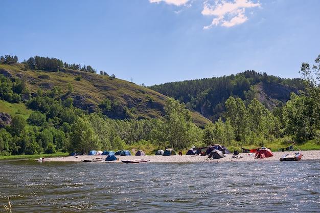 Touristenlager am fluss. zelte unter dem blauen himmel. rafting auf einem gebirgsfluss.