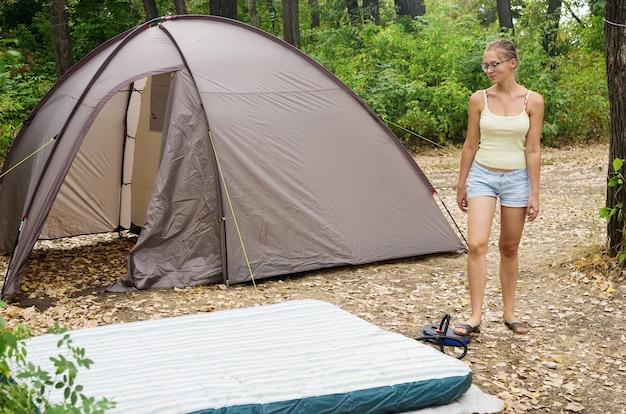 Touristenlager. sie pumpt eine aufblasbare matratze auf