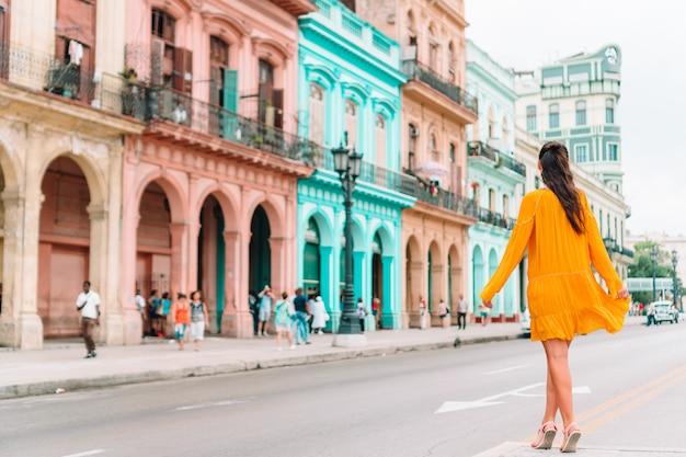 Touristenmädchen in der beliebten gegend in havanna, kuba. rückansicht des lächelnden reisenden der jungen frau