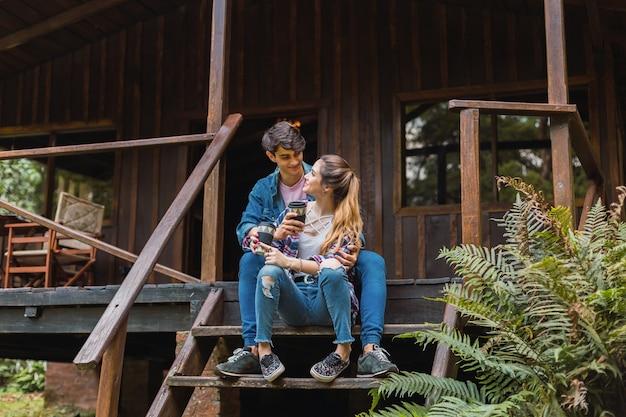 Touristenpaar, das auf der treppe sitzt und kaffee trinkt