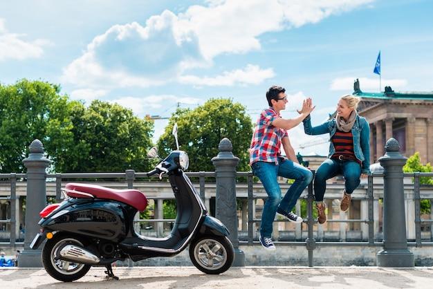 Touristenpaar, das während eines vespa-ausflugs in der nähe der alten nationalgalerie in berlin halt macht