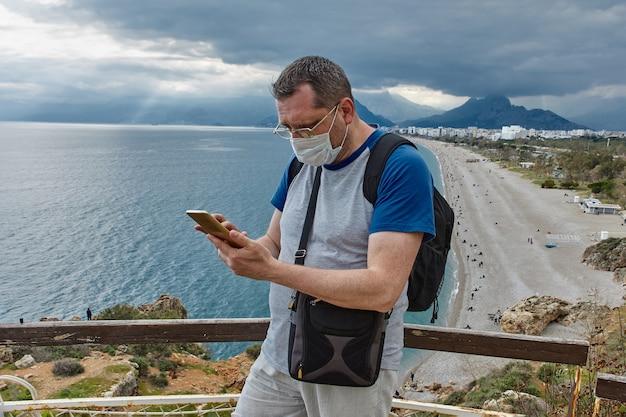 Touristenreise nach türkischem antalya während des koviden pandemiemannes mit gesichtsmaske