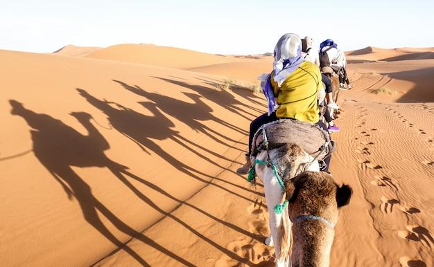Touristenwohnwagen, der dromedare durch sanddünen in sahara-wüste nahe merzuga in marokko reitet